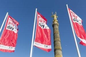 """BPW Germany e.V. Equal Pay Day Foto: Businessfotografie Inga Haar. equal pay day 2016 – Fahnenaktion an der Berliner Siegessäule """"Berufe mit Zukunft"""" – Unter dem Motto: """"Was ist meine Arbeit wert?"""", BPW Germany"""